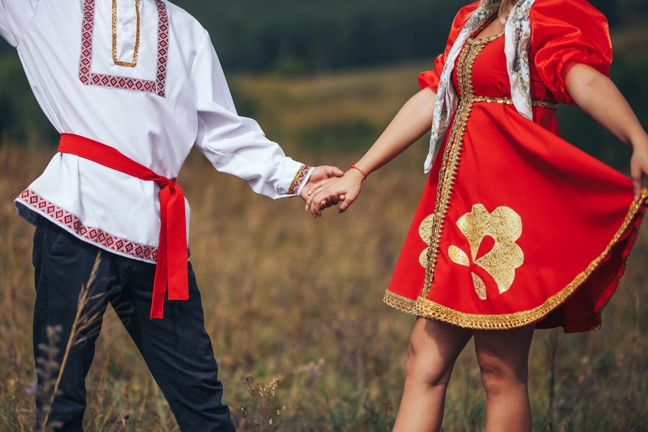 Dancing guy and girl dressed in national Russian clothes are holding hands Art grain and noise on